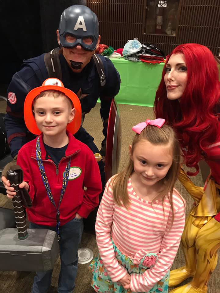 Young girl and boy smiling with Captain America and comic book villainess