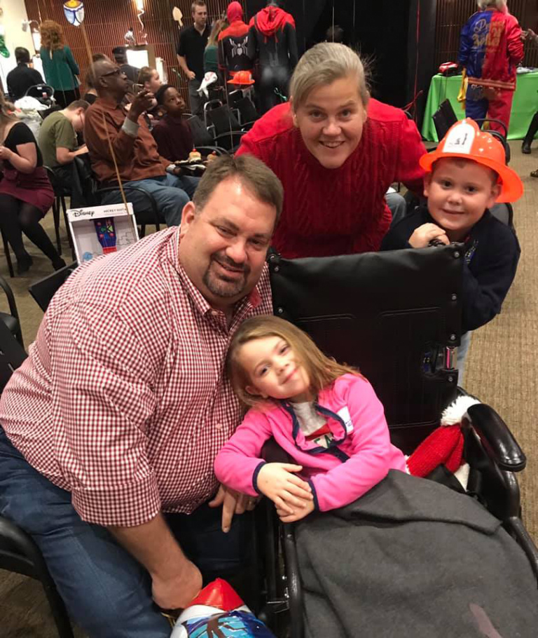 Couple with a young girl in a wheelchair and a young boy with an orange plastic firefighter hat