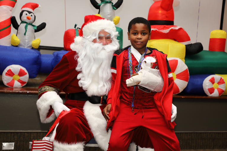 Boy with arm in a sling smiling on Santa's lap