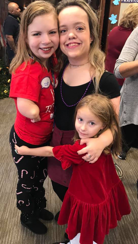 Woman with a girl and a young girl all smiling and hugging
