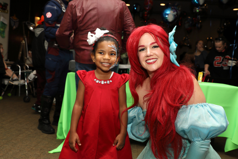 Young girl smiling with Ariel from the Little Mermaid