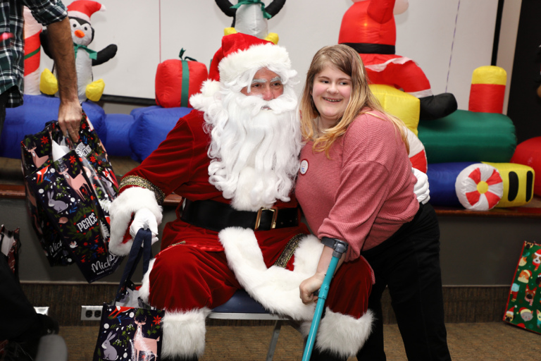 Santa and girl using a forearm crutch smiling