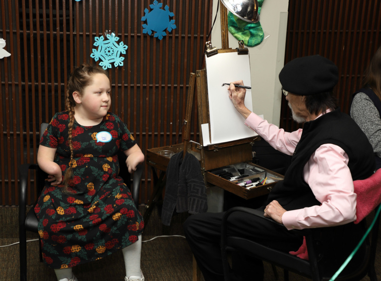 Girl having her caricature drawn by an artist in a beret