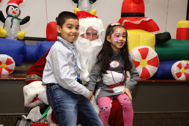 Girl with face painted and boy smiling sitting on Santa's lap