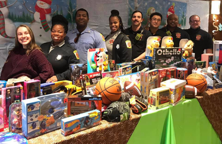 Baltimore City Fire Department staff smiling behind the table of toys they donated for patient families