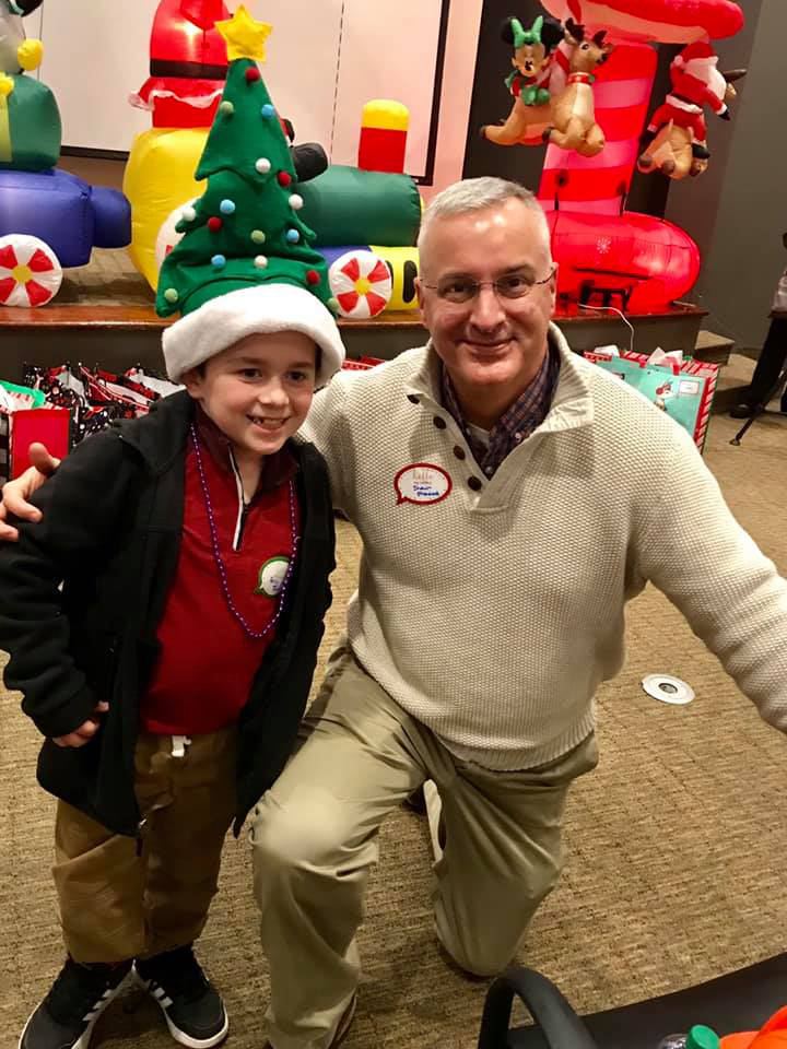 Dr. Shawn Standard kneeling down next to young boy wearing a Christmas tree hat, both smiling