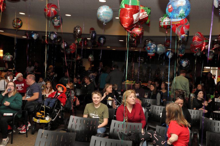 Families sitting in chairs decorated with balloons enjoying the International Center for Limb Lengthening pediatric holiday party