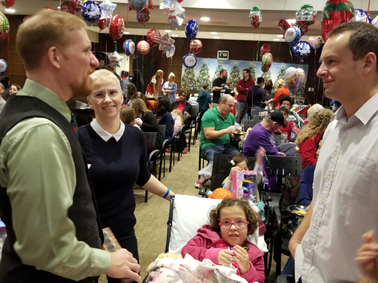 Physician Assistant Chris Fisher talking with patient family at the International Center for Limb Lengthening pediatric holiday party