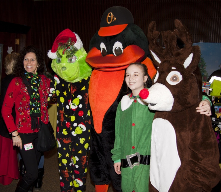 2 Volunteers, one dressed as elf, with Orioles mascot, Grinch character and Rudolph character
