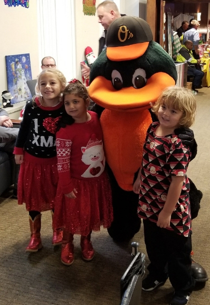 Orioles mascot with three young children in holiday tops