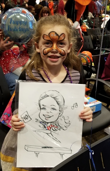 Female child with face painted and caricature drawing at the International Center for Limb Lengthening pediatric holiday party