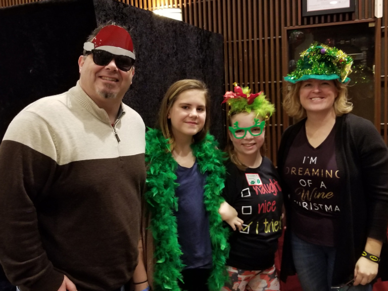 Parents with 2 children dressed in fun holiday-themed photo booth accessories at the International Center for Limb Lengthening pediatric holiday party