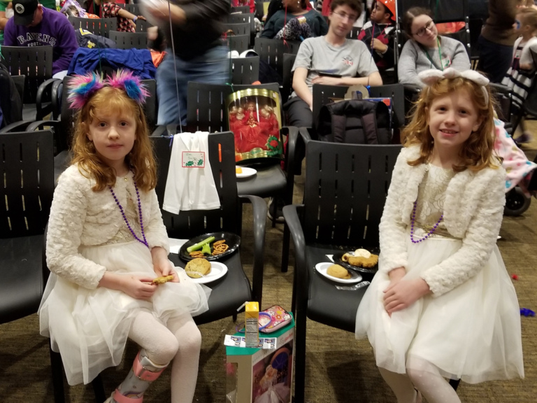 2 young girls twins, one wearing leg brace, in matching white dresses enjoying food at the International Center for Limb Lengthening pediatric holiday party
