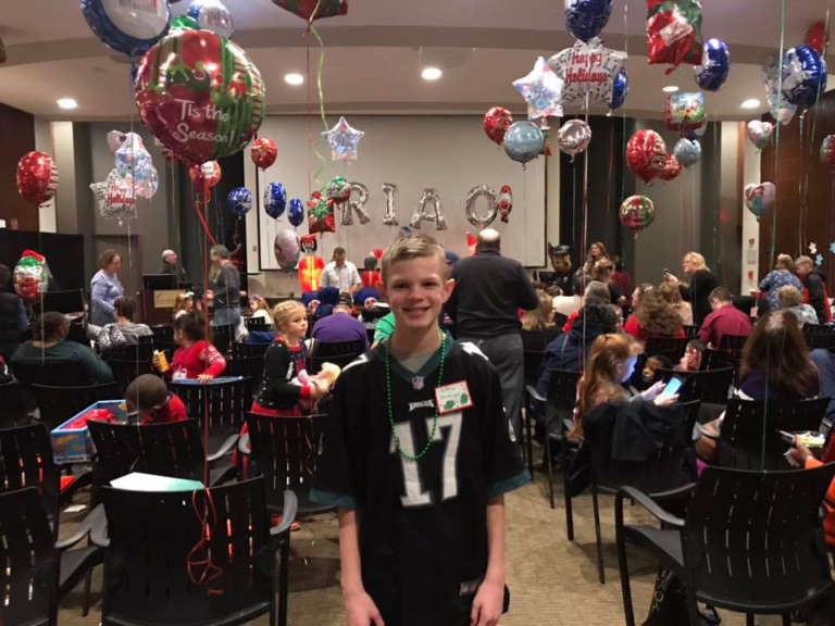 Male child smiling in front of chairs decorated with balloons at the International Center for Limb Lengthening pediatric holiday party