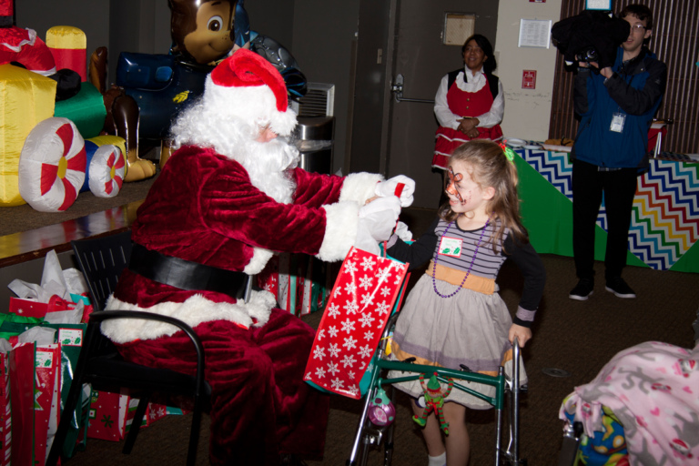 Santa gives present to girl patient with a walker at the International Center for Limb Lengthening pediatric holiday party