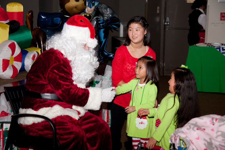 Santa talking to 3 girls at the International Center for Limb Lengthening pediatric holiday party