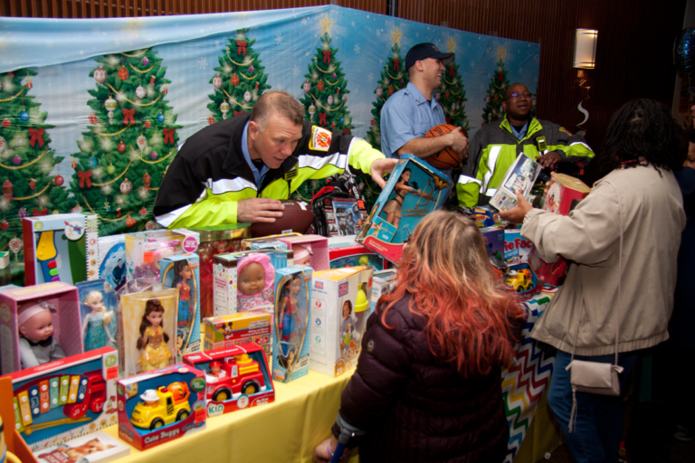 Firemen handing out toys to patients at the International Center for Limb Lengthening pediatric holiday party