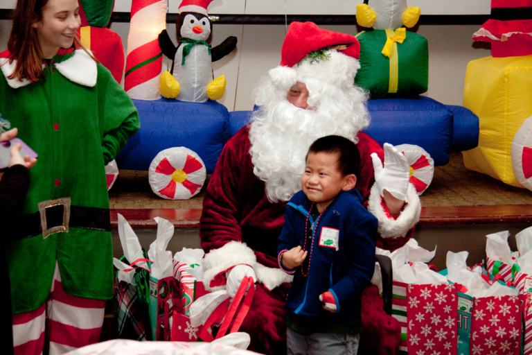 Santa and elf posing with young boy in hand cast at the International Center for Limb Lengthening pediatric holiday party
