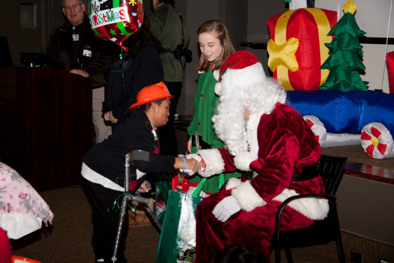 Santa shaking hands with patient on forearm crutches at the International Center for Limb Lengthening pediatric holiday party