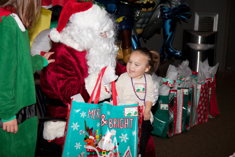 Santa gives present to young girl at the International Center for Limb Lengthening pediatric holiday party
