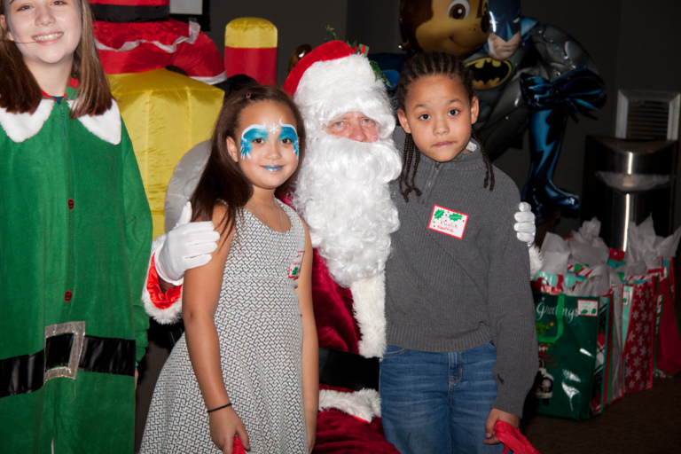 Santa and elf pose for picture with 2 children, one wearing face makeup, at the International Center for Limb Lengthening pediatric holiday party