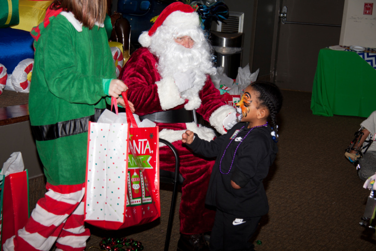 Santa and elf present a present to young girl with face painted as tiger at the International Center for Limb Lengthening pediatric holiday party