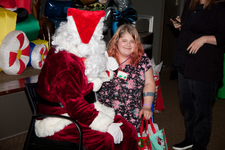 Santa talks with girl with forearm crutches and present at the International Center for Limb Lengthening pediatric holiday party