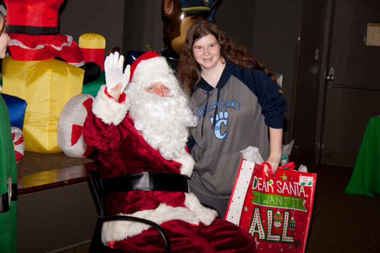 Santa waves and poses with girl with present at the International Center for Limb Lengthening pediatric holiday party