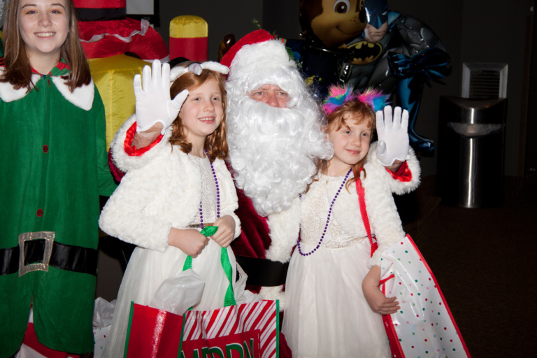 Santa and elf pose with 2 girls in white dresses with gifts at the International Center for Limb Lengthening pediatric holiday party