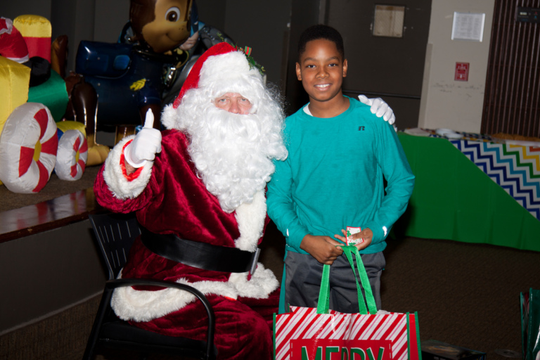 Santa gives a thumbs up with boy with present at the International Center for Limb Lengthening pediatric holiday party