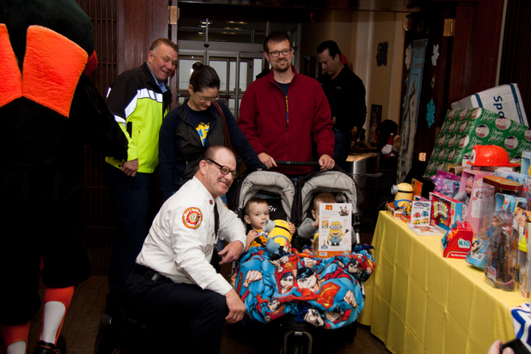 Fireman giving twin boys in strollers Minions toys at the International Center for Limb Lengthening pediatric holiday party