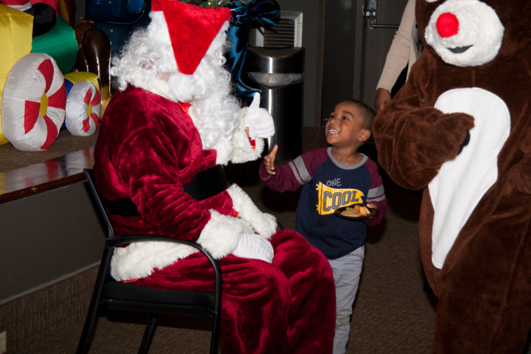 Santa greets young boy with food at the International Center for Limb Lengthening pediatric holiday party