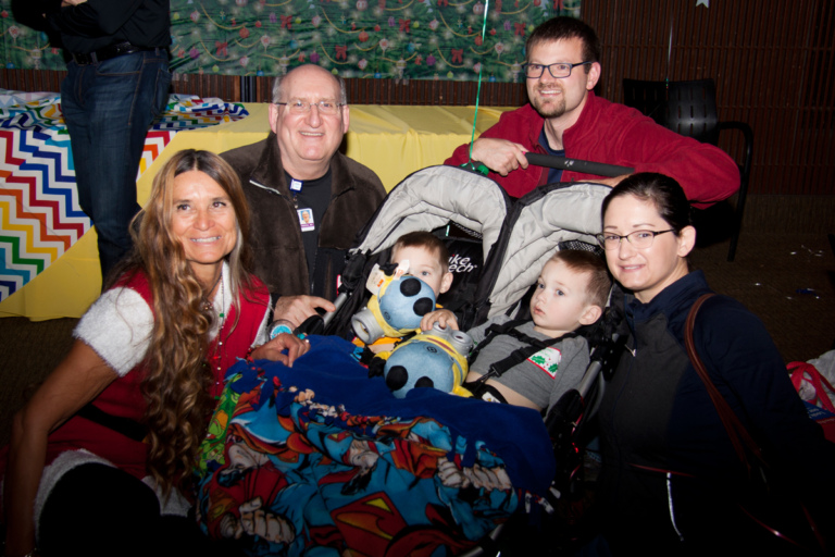Dr. John Herzenberg and Marilyn Richardson, Pediatric Liaison, with a family with twin boys in strollers at the International Center for Limb Lengthening pediatric holiday party