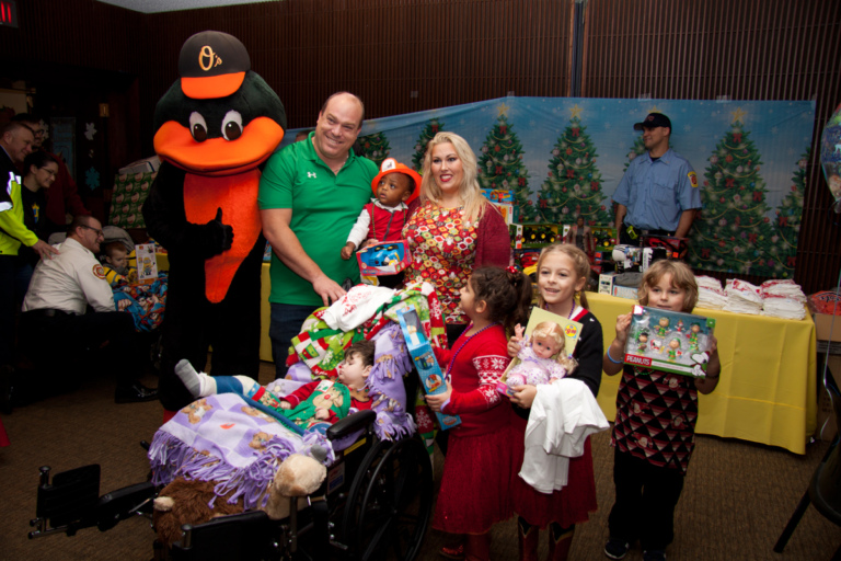 Parents with 4 young children with gifts and one sleeping child wearing casts in a wheelchair at the International Center for Limb Lengthening pediatric holiday party