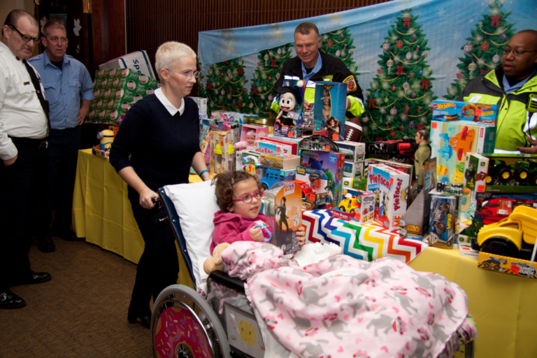 Mom wheeling young girl in wheelchair looking at toy received from firemen's toy display table at the International Center for Limb Lengthening pediatric holiday party