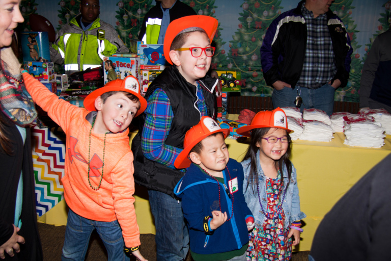 4 young kids smiling wearing toy orange firefighter hats at the International Center for Limb Lengthening pediatric holiday party