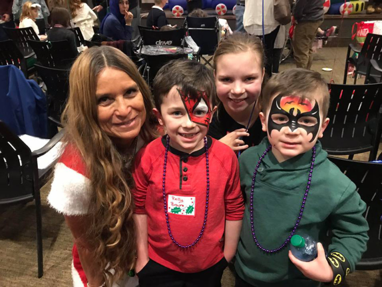 Marilyn Richardson, Pediatric Liaison, with one girl and two boys wearing superhero face paint at the International Center for Limb Lengthening pediatric holiday party