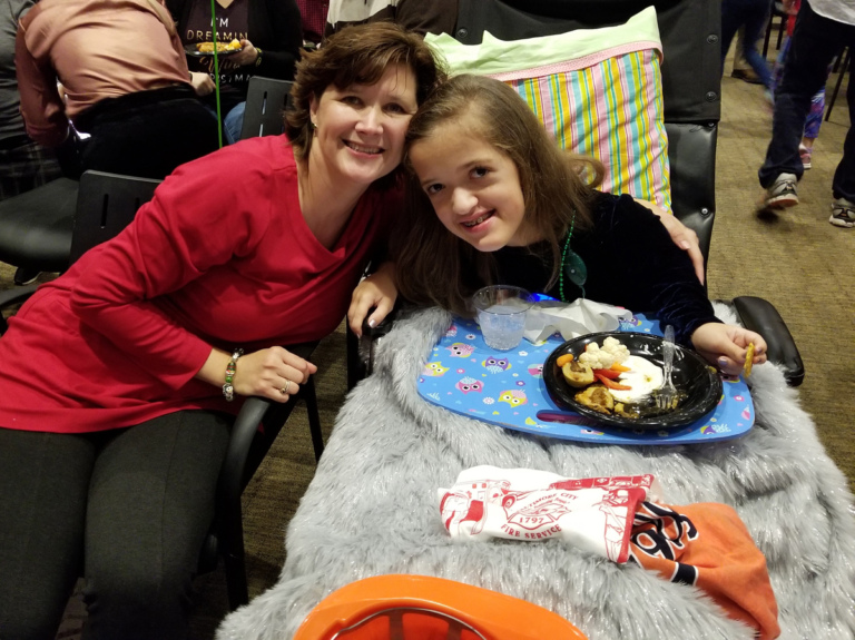 Mom and daughter in wheelchair enjoying food at the International Center for Limb Lengthening pediatric holiday party