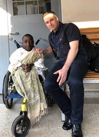 Buru in a wheelchair smiling with Dr Christof Radler