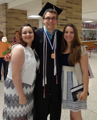 Chase at his high school graduation with his sisters