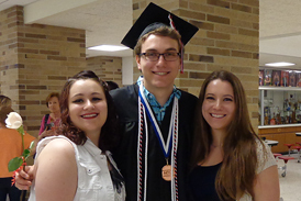 Chase in graduation cap and gown with his two sisters