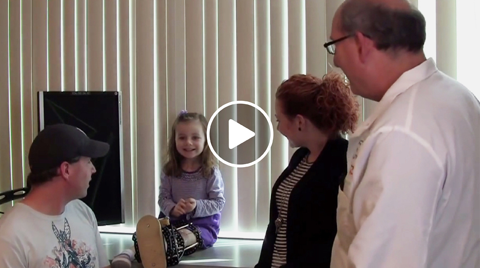 Fibular hemimelia patient with an external fixator on her leg talking to Dr. John Herzenberg at the International Center for Limb Lengthening