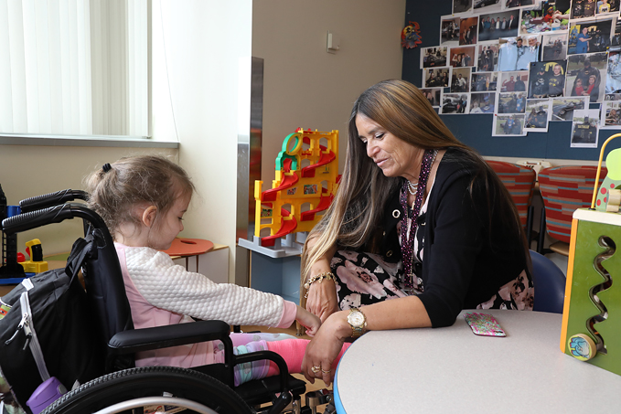 International Center for Limb Lengthening Child Life Specialist Marilyn Richardson comforting a young girl in a wheelchair in clinic waiting area