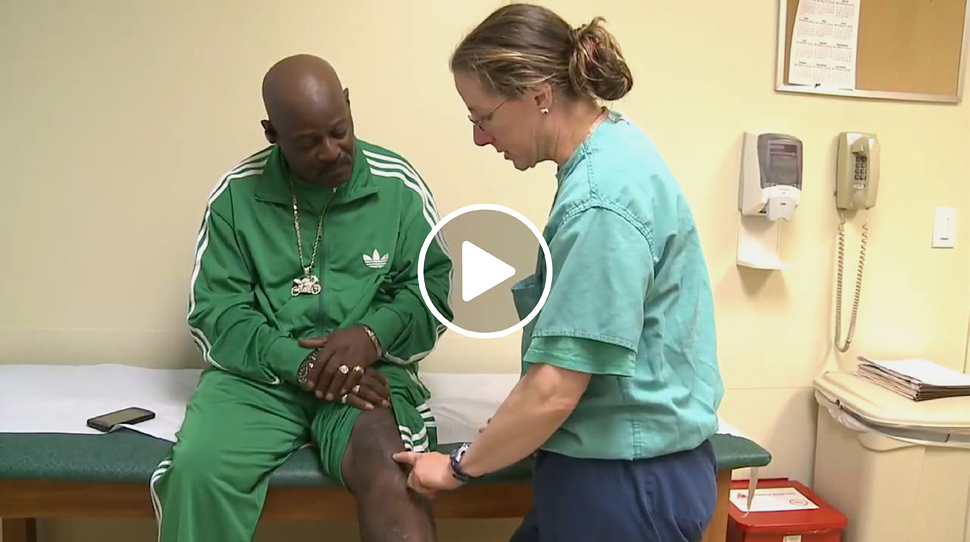 Picture from video of Dr. Janet Conway checking a male patient's leg