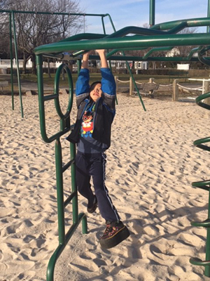 Primo with a shoe lift playing on the monkey bars