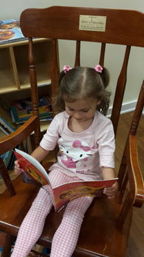 Anicka using her treated hand holding open a book on a rocking chair