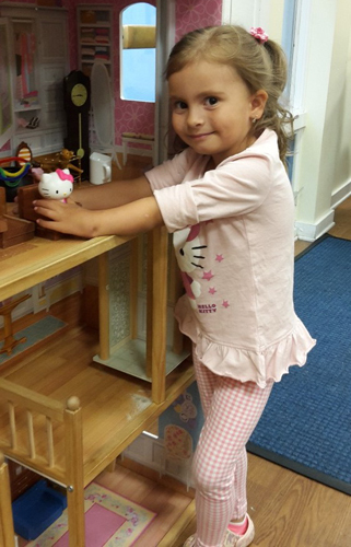 Anicka using her treated hand to play with toys