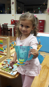Anicka using her treated hand to hold a play pitcher