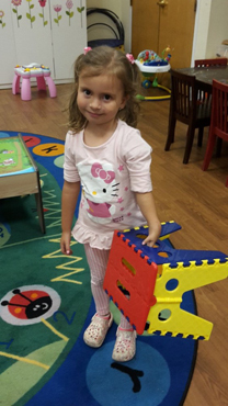 Anicka using her treated hand to hold up a play stool in a play room