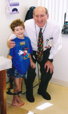 Christopher as young boy wearing external fixator with Dr. Herzenberg at International Center for Limb Lengthening
